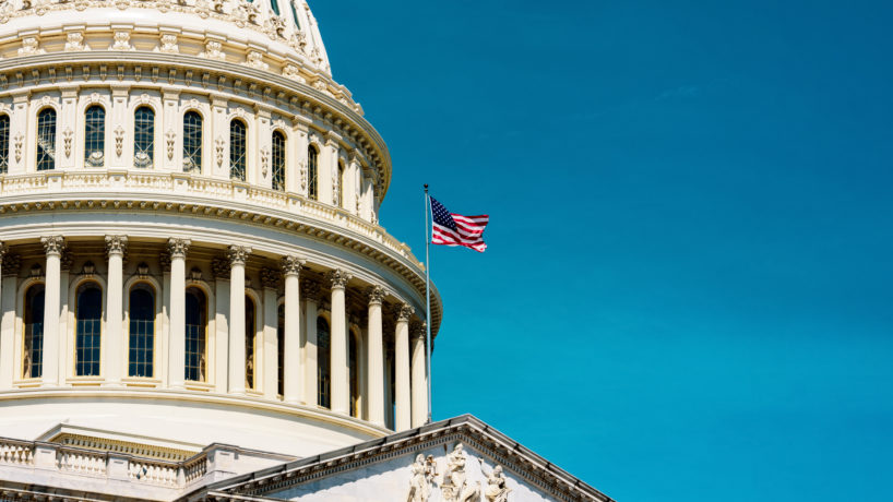A Picture of the United States Capitol in Washington D.C. is featured against the background of a blue sky.