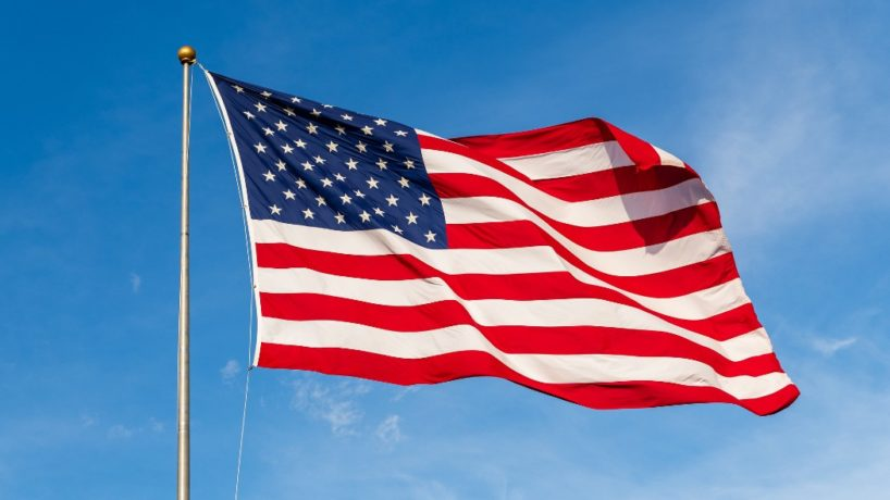 American Flag Waves Against a Blue Sky Background