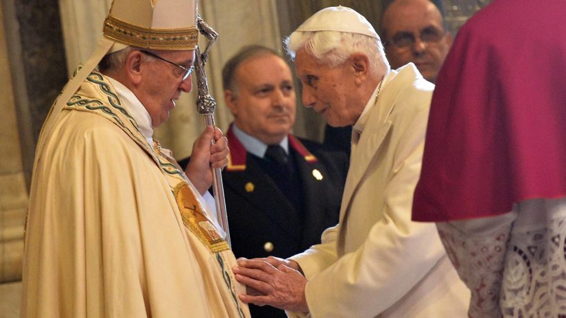 Pope Emeritus Benedict XVI speaks to Pope Francis at a ceremony at the Vatican in 2015.
