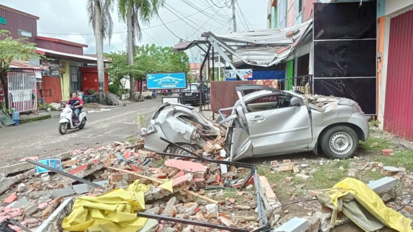 A destroyed car sits amongst debris on the side of a street in Mamuju on January 15, 2021, after a 6.2-magnitude earthquake rocked Indonesia's Sulawesi island.