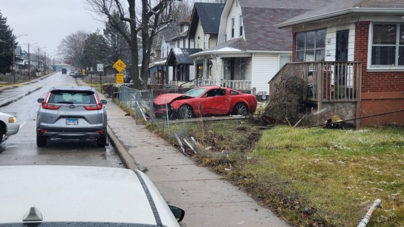 A red car crashed into a fence