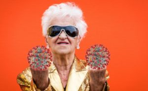 an old woman against an orange background gives the finger to the camera
