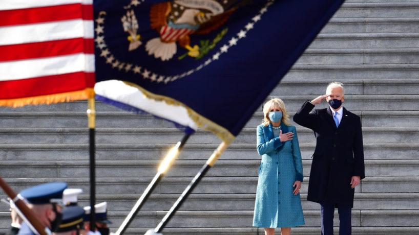 Joe Biden saluting military flags