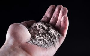 People hand holding gray ash isolated on black. Close up. Selective focus