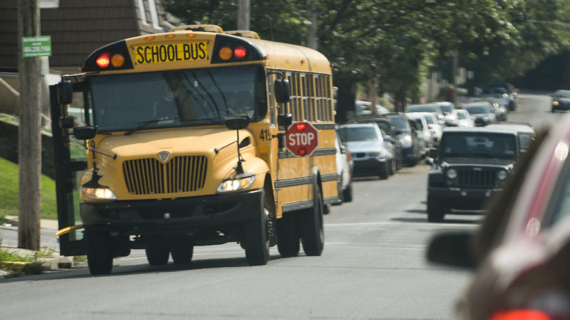 A school bus stopping to pick up a kid.