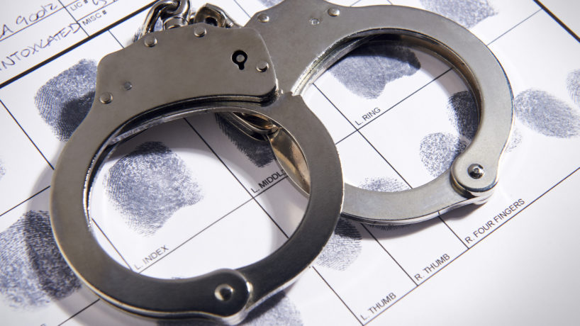 Handcuffs laying on top of fingerprint chart in file
