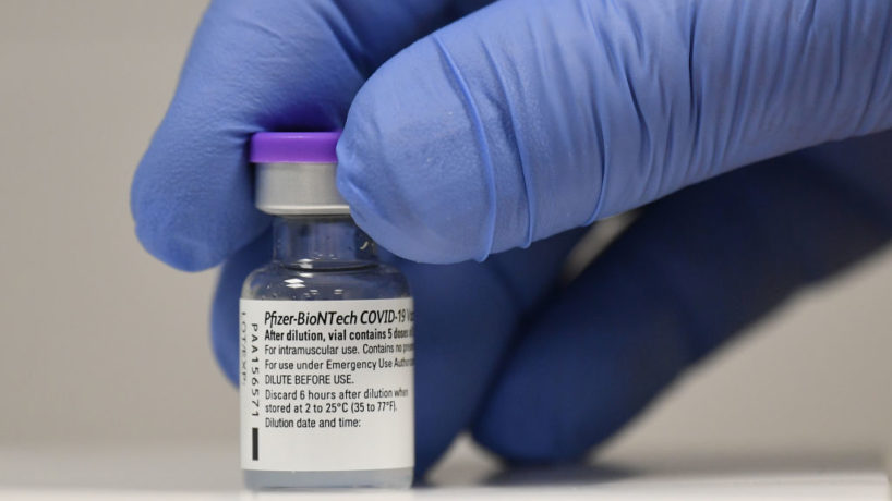 A member of staff poses with a phial of Pfizer-BioNTech Covid-19 vaccine at a vaccination health centre in Cardiff, Wales.
