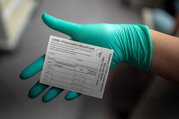 A healthcare worker displays a COVID-19 vaccine record card at the Portland Veterans Affairs Medical Center on December 16, 2020 in Portland, Oregon.