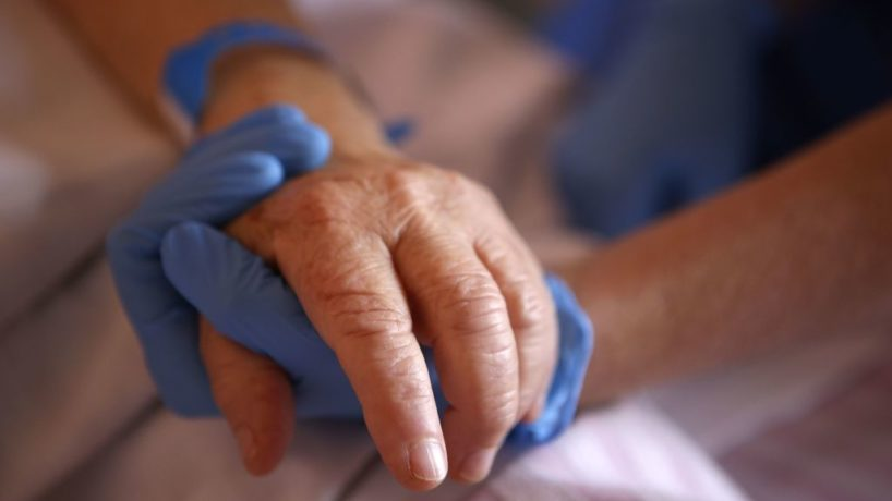 A nurse wearing protective gloves holds the hand of a patient in the palliative care unit of the the Eugenie Hospital in Ajaccio, on the French Mediterranean island of Corsica, on April 23, 2020.