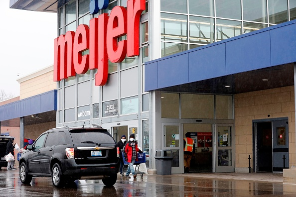 People wear face masks as they leave a Meijer store in Detroit, Michigan on April 7, 2020.