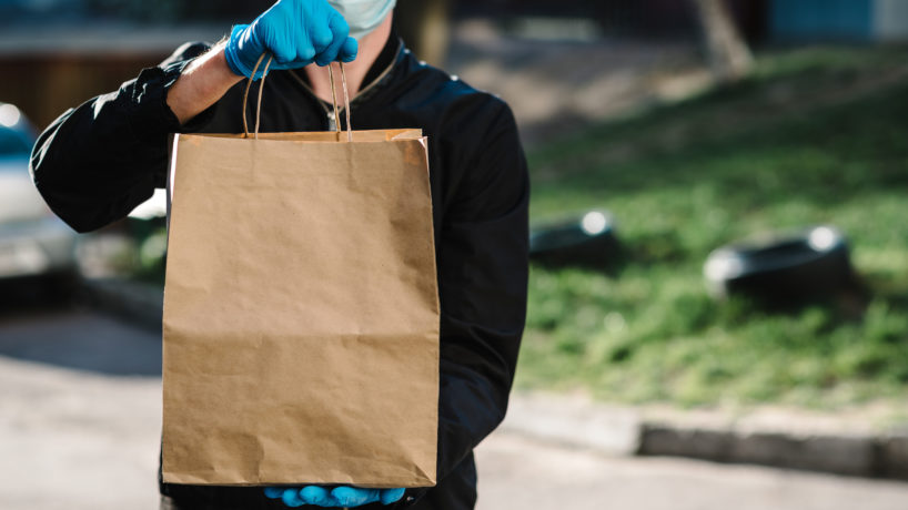 Courier in protective mask, medical gloves delivers takeaway food.