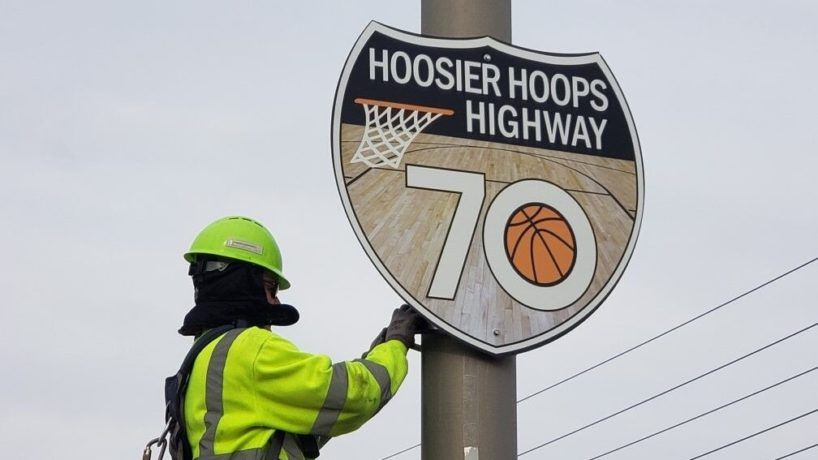 """An INDOT worker installing a """"Hoosier Hoops Highway"""" sign along Interstate 70 in Indiana."""