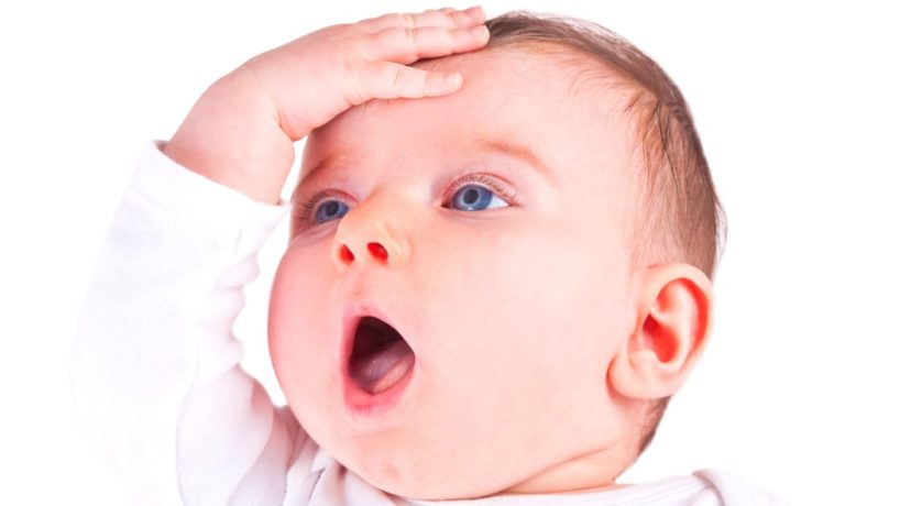 An infant with bright blue eyes smacks his forehead in disbelief.