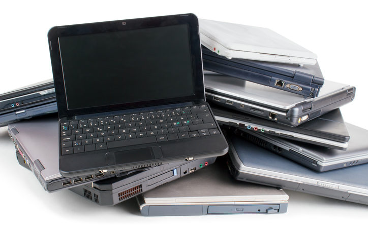 A stack of used laptop computers.
