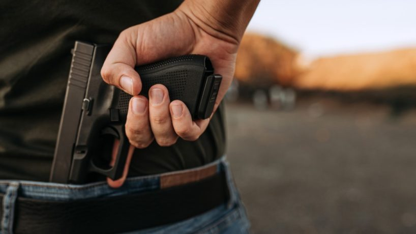 Man holds a handgun, pulling it out of his waistband.