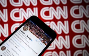 Donald Trump's Twitter timeline is seen on a smartphone against a backdrop with the CNN logo, in Ankara, Turkey on December 9, 2018.