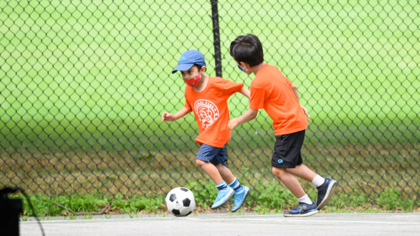 Kids wear face masks while playing soccer in Central Park as the city continues Phase 4 of re-opening following restrictions imposed to slow the spread of coronavirus