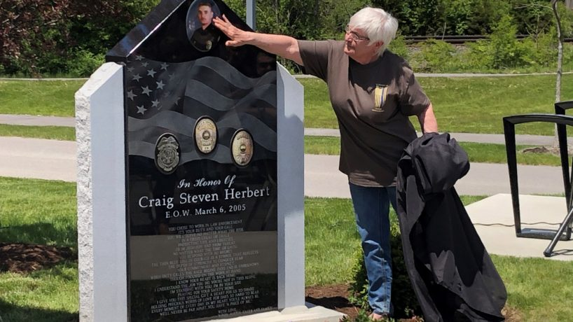 Andy Macy, mother of fallen Lawrence police officer Craig Herbert, touches her son's photograph on a memorial monument unveiled at Lawrence police headquarters.