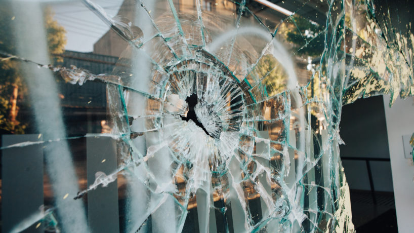 broken glass window as a result of riots.