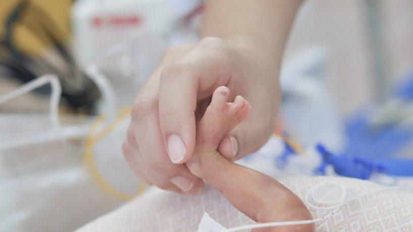 Hand taking premature baby foot, at chidren's hospital.