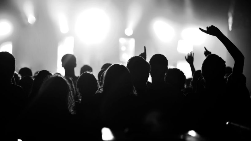 A general view of a rock concert taken from the back of a venue showing the audience in silhouette raising their arms and cheering with bright light shining from the stage in circa 2010.