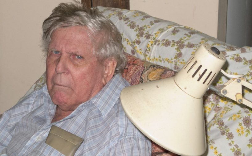 Grumpy Senior Man sitting on a comfy chair with a cushion behind him and an old lamp beside him, in Queensland, Australia