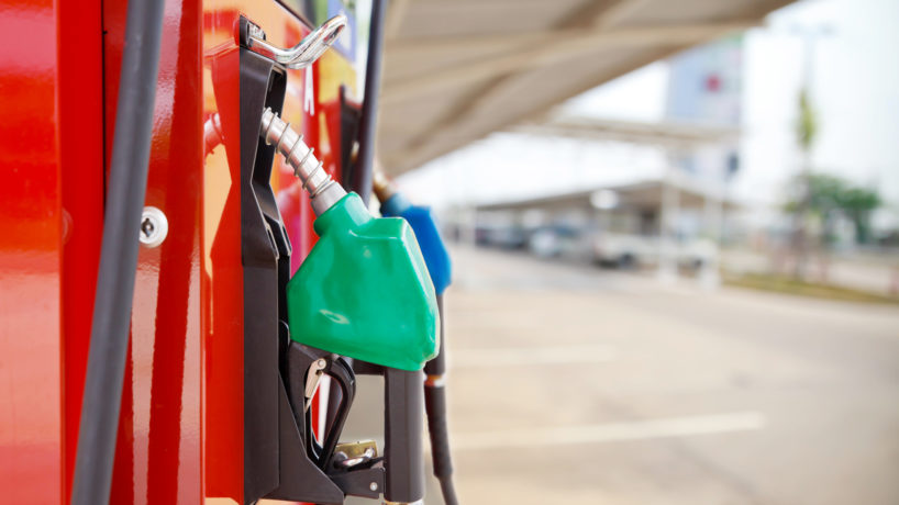 A car filling up with gasoline at a gas station showing a close up of the pump in the gas tank from a side view.