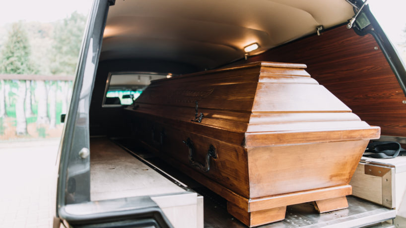 photo of a coffin car at a funeral heading to the graveyard