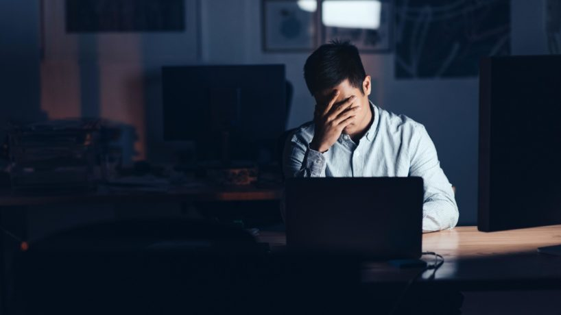 A stressed out man sitting at a desk.