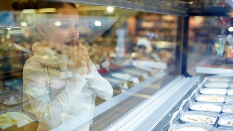 Amazed child looking at showcase with ice-cream assortment