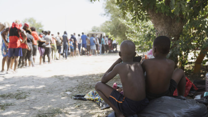 Migrants wait in line for supplies in a park near the Del Rio-Acuna Port of Entry in Acuna, Coahuila state, Mexico, on Monday, Sept. 20, 2021. The U.S. flew Haitians camped in a Texas border town back to their homeland Sunday and tried blocking others from crossing the border from Mexico in a massive show of force that signaled the beginning of what could be one of America's swiftest, large-scale expulsions of migrants or refugees in decades, reports the Associated Press. Photographer: Eric Thayer/Bloomberg via Getty Images
