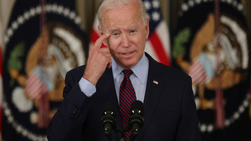 Biden at podium pointing to his head