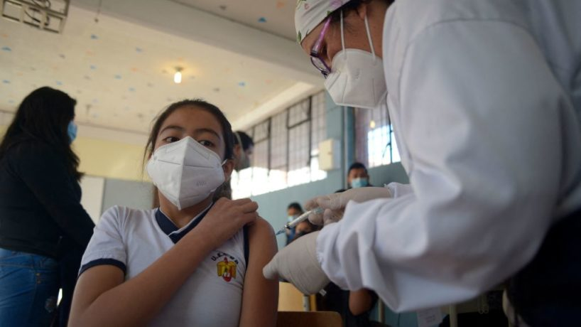 A health worker inoculates a child against COVID-19 with a dose of the CoronaVac vaccine, developed by China's Sinovac firm, at a school in Quito on October 18, 2021, as the country began inoculating children aged 5 to over 11.