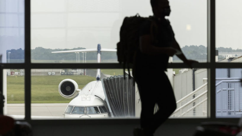 A traveler wearing a protective face mask waits to board a flight at Springfield-Branson National Airport (SGF) in Springfield, Missouri, U.S., on Thursday, Aug. 5, 2021.