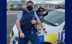 """Screen Capture shows a New Zealand police officer sitting with a child who called """"111"""""""