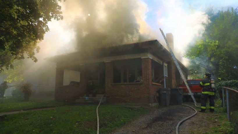 Heavy smoke flows from the back of the house that's on fire on 32nd Street