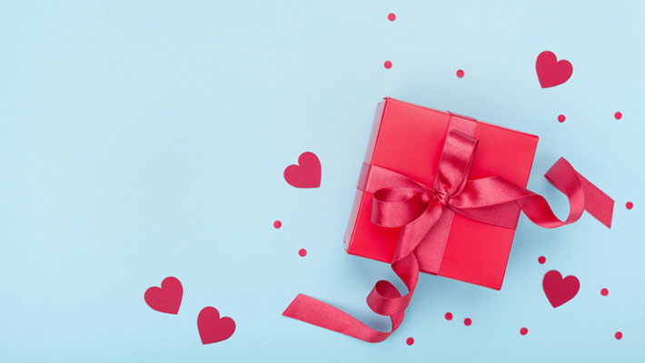 Present or gift box, paper heart and confetti on blue background top view. Valentines day greeting card.