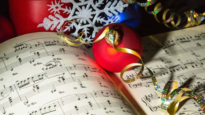 Sheet music surrounded with Christmas ornaments and ribbons