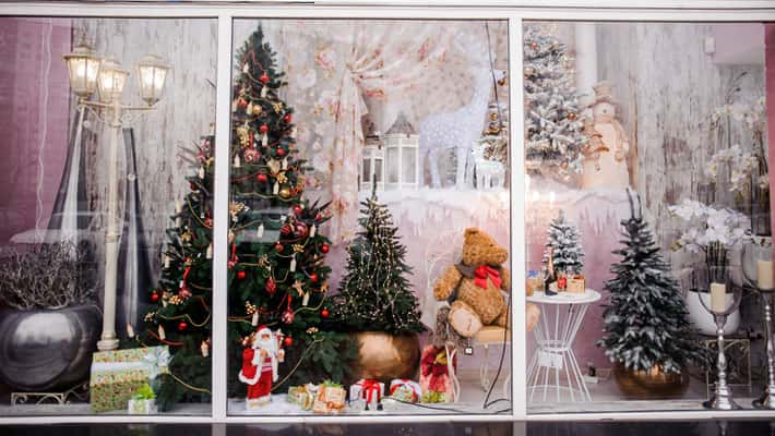 Beautiful festive Christmas storefront with decorated artificial Christmas trees and toys on the pink background