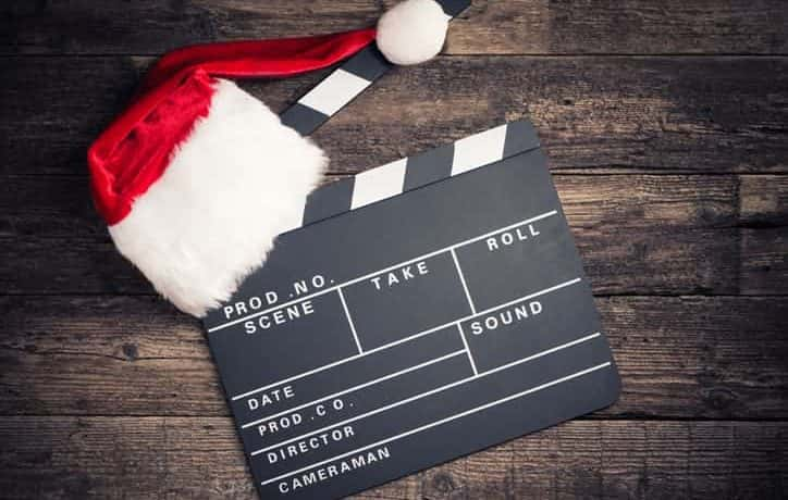 Movie clapboard with a Santa hat on top of it