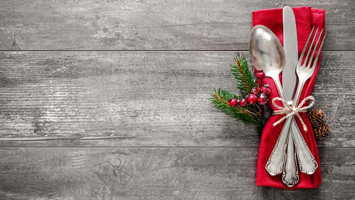 Christmas table place setting on grey wood background