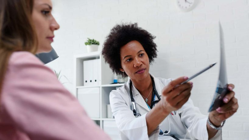 female african american doctor showing white woman patient a document with pen pointing