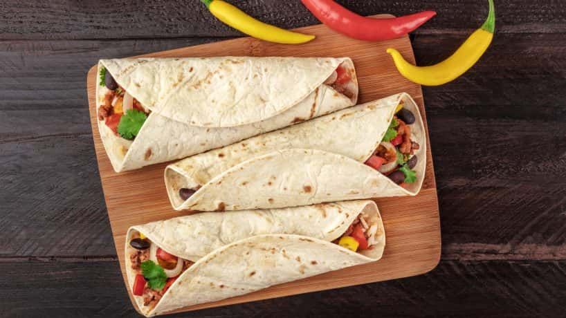 Mexican burritos with chili peppers, and copyspace An overhead photo of Mexican burritos with beef, rice, black beans and vegeta