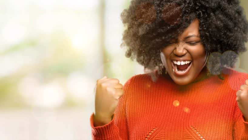 Beautiful african woman happy and excited celebrating victory expressing big success, power, energy and positive emotions. Celeb