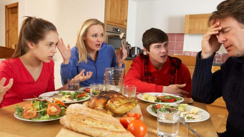 Teenage Family Having Argument Whilst Eating Lunch Together In Kitchen Shouting At Each Other Sitting At Table
