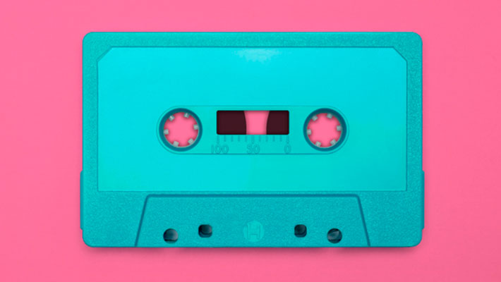 Nostalgic image of a blue cassette tape, isolated and presented on a pink background