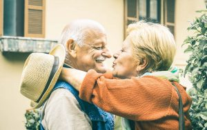 Happy senior retired couple having fun kissing outdoors at travel vacation - Love concept of joyful elderly and retirement lifes