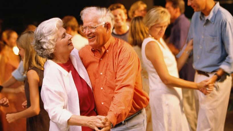 Man and woman dancing among a group of people - stock photo