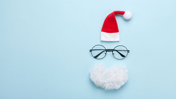 Santa hat, beard and glasses on blue background top view