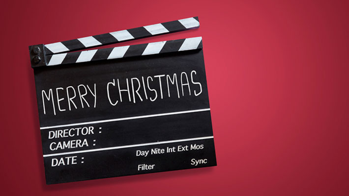 Christmas text title on movie Clapper board on red background
